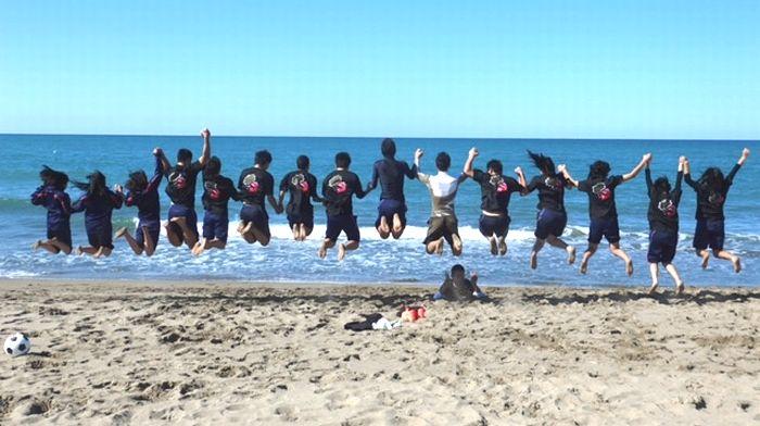 砂浜でオリジナルTシャツを着てジャンプ
